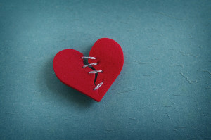 A red heart broken with threaded stitches